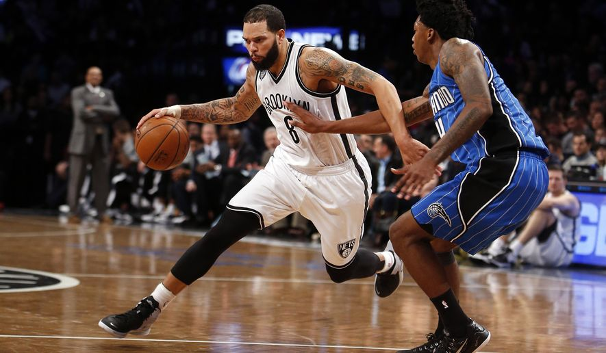 FILE -  In this Nov. 9, 2014, file photo, Brooklyn Nets' Deron Williams (8) drives against Orlando Magic's Elfrid Payton during an NBA basketball game in New York. Two people with knowledge of the arrangement tell The Associated Press that  Williams is set to join the Dallas Mavericks if the point guard clears waivers after reaching a buyout with the Nets. Williams will sign with the Mavericks once he clears waivers Monday, the people said Friday on condition of anonymity because the deal can't become official until Williams clears waivers. (AP Photo/Jason DeCrow, File)