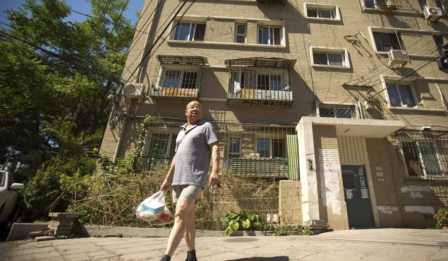 In this Thursday, June 18, 2015 photo, a man walks outside a building in Beijing where an apartment is listed in Chinese official documents as being registered to Xu Ting, her younger brother Xu Lei, and their mother Zhao Peiyuan. Xu Ting, a Chinese immigrant living in the U.S has been sued for counterfeiting by eight different luxury brands, including Gucci and Louis Vuitton, and still owes Chanel Inc. $6.9 million in damages for counterfeiting, according to U.S. court documents. None of this has stopped her from becoming a lawful permanent resident of the United States and amassing the trappings of a solid middle class life. (AP Photo/Mark Schiefelbein)