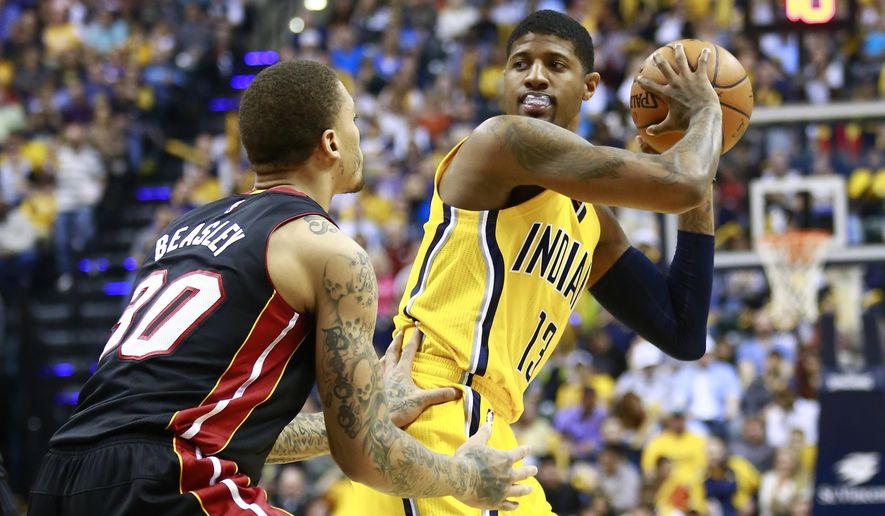 FILE - In this April 5, 2015 file photo, Indiana Pacers forward Paul George, right, controls the ball as Miami Heat forward Michael Beasley defends in the second half of an NBA basketball game in Indianapolis. George is too busy this summer to reflect much on his gruesome leg injury. Eleven months after the injury ruined his season and derailed the Pacers' title hopes, George has moved on. He's dunking off both feet, following his traditional training regimen and preparing for another NBA season with a new cast of teammates - all without giving his broken right leg a second thought. (AP Photo/R Brent Smith, File)