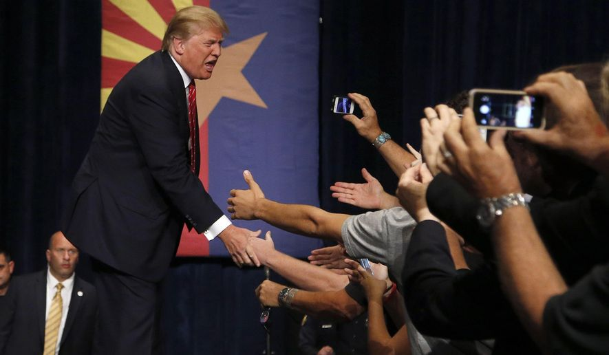 Republican presidential candidate Donald Trump shakes hands prior to speaking at a rally before a crowd of 3,500 Saturday, July 11, 2015, in Phoenix. (AP Photo/Ross D. Franklin)