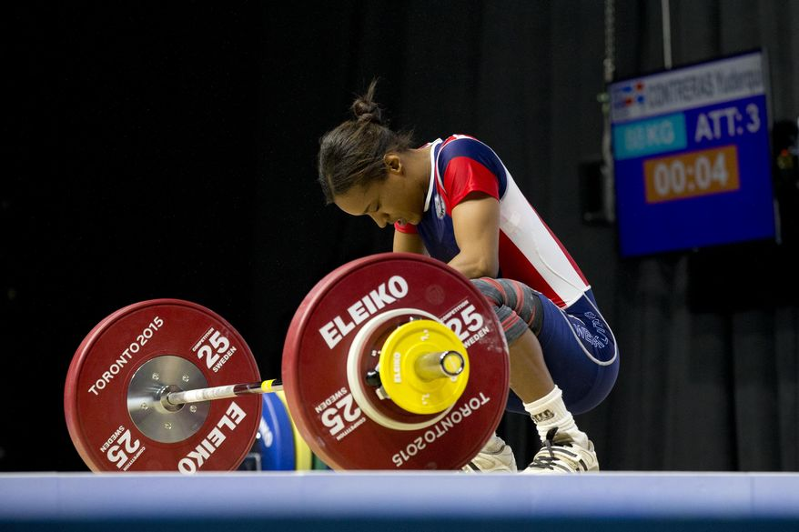 Pan Am record holder Yuderquis Contreras of Dominican Republic reacts after failing her third snatch attempt in the women's 53kg weightlifting event at the Pan Am Games in Oshawa, Ontario, Sunday, July 12, 2015. (AP Photo/Rebecca Blackwell)