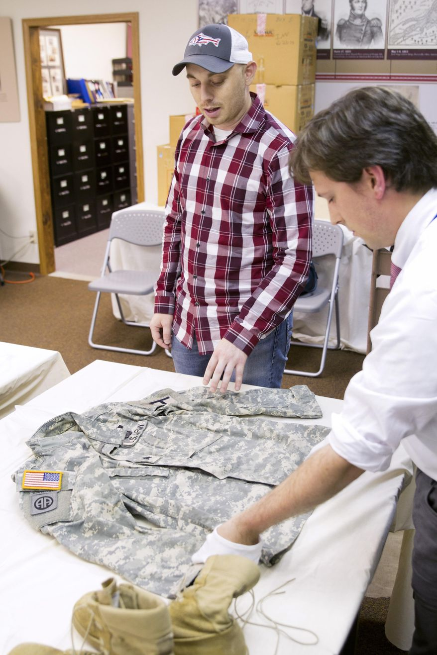 In this June 26, 2015, photo provided by the Ohio History Connection,Army veteran Kevin Lang, center, shows curator Eric Feingold, right, features of his Army jacket after donated the items at the Ohio History Connection collections center in Columbus, Ohio. The state's history organization is launching a statewide effort to preserve and showcase Ohio's military past by encouraging donated items and stories from current and past military service members and their families. (Ty Pierce/Ohio History Connection via AP)
