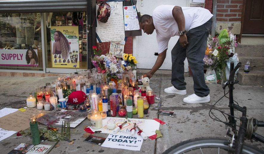 FILE - In this July 22, 2014, file photo, a mourner places a candle at a memorial for Eric Garner, who died while being arrested by New York City police, in Staten Island. Nearly a year has passed since Garner had the encounter with police that led to his death. Since then, his family has become national advocates for police reform and the department is changing how it relates to the public it serves. (AP Photo/John Minchillo. File)