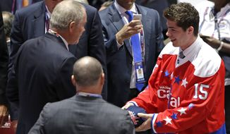 Connor Hobbs, front right, receives a cap from team after being chosen 143rd overall by the Washington Capitals during the fifth round of the NHL hockey draft, Saturday, June 27, 2015, in Sunrise, Fla. (AP Photo/Alan Diaz)