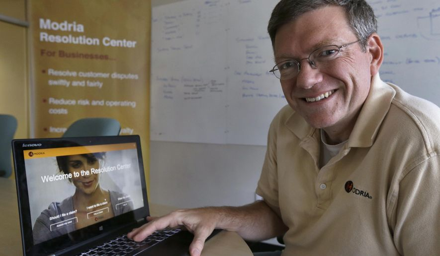 In this July 2, 2015 photo, Colin Rule, CEO of Modria, poses with the Modria resolution software operating on his laptop at his company's  headquarters in San Jose, Calif. Experts say Modria is at the forefront of the next wave of legal technology in which laws are translated into computer code that can solve potential legal battles without the need for a judge or attorney. (AP Photo/Ben Margot)