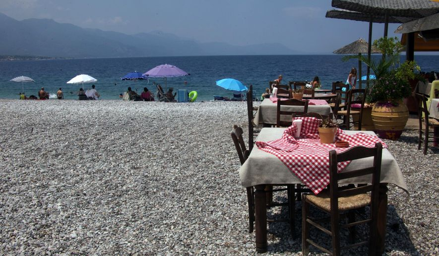 In this photo taken on Saturday, July 11, 2015, bathers lie on the beach in front of a restaurant in the village of Psatha about 65km (40 miles) west of Athens. The meal sales tax clause in the bailout proposal considered Sunday by European leaders would boost it from 13 percent to 23 percent, while hotels would see room sales taxes rise from 6.5 percent to 13 percent. (AP Photo/Spyros Tsakiris)