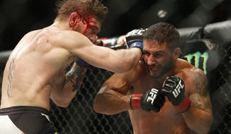 EDS NOTE GRAPHIC CONTENT - Conor McGregor, left, hits Chad Mendes during their interim featherweight title mixed martial arts bout at UFC 189 Saturday, July 11, 2015, in Las Vegas. (AP Photo/John Locher)