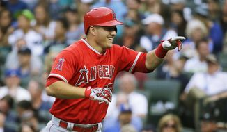 Los Angeles Angels' Mike Trout smiles after hitting a three-run home run in the third inning of a baseball game against the Seattle Mariners, Friday, July 10, 2015, in Seattle. (AP Photo/Ted S. Warren)