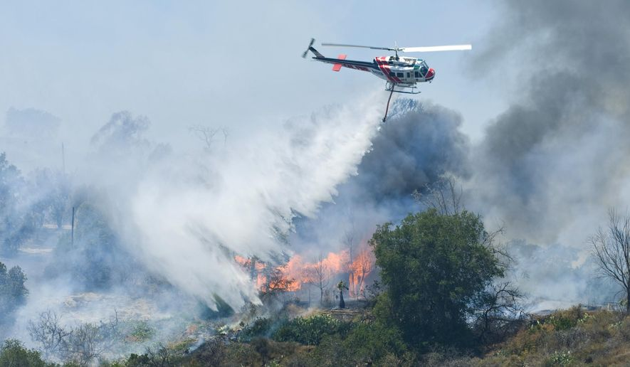 A helicopter drops water on a burning structure at Irvine Lake during the firefighting efforts on Monday, July 13, 2015, in Orange County, Calif. County fire officials say the blaze broke out Thursday in the unincorporated Silverado Canyon area near Irvine Lake. (Sam Gangwer/The Orange County Register via AP)   MAGS OUT; LOS ANGELES TIMES OUT; MANDATORY CREDIT