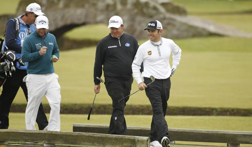 South Africa's George Coetzee, centre, Louis Oosthuizen, right, and Branden Grace walk towards the 1st green during a practice round  at the Old Course, St Andrews, Scotland, Monday, July 13, 2015. The  2015 Open Golf Championship that is due to take place at St. Andrews July16-19.  (AP Photo/Peter Morrison)