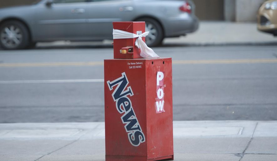 A Detroit News newspaper box is left outside a building housing the offices of the Detroit Free Press and The Detroit News on Sunday, July 12, 2015 in Detroit. Police say the box posed no threat and the building was reopened after being evacuated earlier.  (David Guralnick/Detroit News via AP)  DETROIT FREE PRESS OUT; HUFFINGTON POST OUT