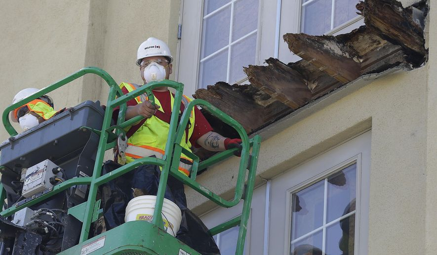 FILE - In this June 18, 2015 file photo a crew works on the remaining wood of an apartment building balcony that collapsed killing six college students and injuring several others in Berkeley, Calif.  State Sens. Loni Hancock, D-Berkeley and Jerry Hill, D-San Mateo,  have introduced legislation that would require construction companies to disclose felony convictions or legal settlements alleging construction defects to state regulators.  The bill, SB465, comes in response to an apartment building balcony collapse in Berkeley, that killed six young people in June. (AP Photo/Jeff Chiu, File)