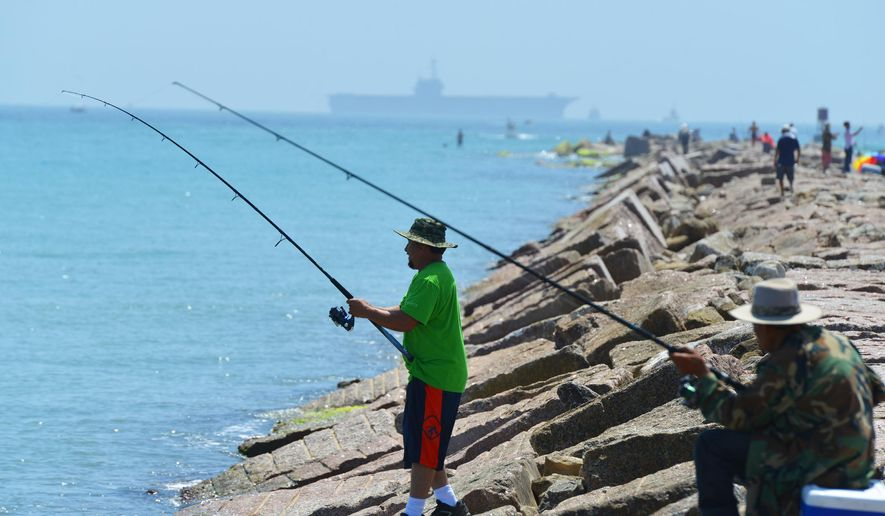 Fishermen cast their rods Sunday, July 12, 2015, as the USS Ranger arrives at South Padre Island, Texas. (Miguel Roberts/The Brownsville Herald via AP)
