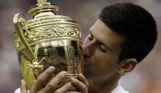 Novak Djokovic of Serbia kisses the trophy after winning the men's singles final against Roger Federer of Switzerland at the All England Lawn Tennis Championships in Wimbledon, London, Sunday July 12, 2015. Djokovic won the match 7-6, 6-7, 6-4, 6-3. (AP Photo/Alastair Grant)