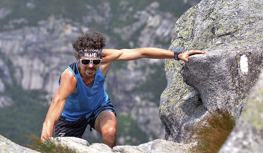 In this Sunday, July 12, 2015 photo released by the Brooks Running Company, Scott Jurek, of Boulder, Colo., climbs to the summit of Mount Katahdin near Millinocket, Maine, before completing the Appalachian Trail in what he claims is record time. Jurek, winner of several ultramarathon races, began at Springer Mountain in northern Georgia on May 27. (Luis Escobar/Brooks Running Company via AP)