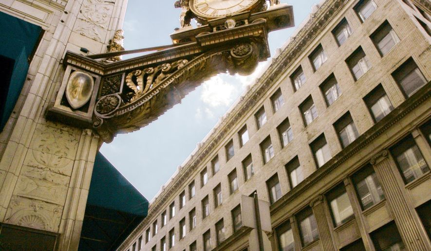 FILE - In this July 28, 2005 file photo pedestrians walk under the clock at former Kaufmann's department store and present day Macy's in downtown Pittsburgh.  Macy's is closing its downtown Pittsburgh location after selling the landmark building where the now-defunct Kaufmann's chain ran its flagship store for more than a century, the retailer said Monday, July 13, 2015. Core Realty, a Philadelphia-based developer, purchased the 13-story building and is planning a hotel and residential project, Macy's said. (AP Photo/Keith Srakocic, File)