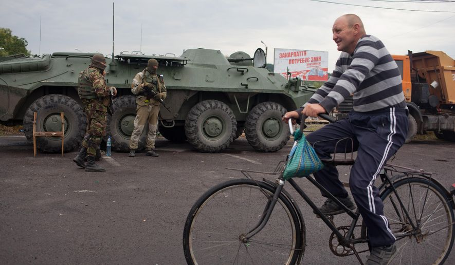 A local man on a bike passes by APCs that block the traffic near the western Ukrainian city of Mukacheve Monday, July 13, 2015. At least two people were killed Saturday in a gun and grenade attack in Mukacheve involving the country's notorious nationalist militia Right Sector. Police had surrounded some gunmen in a wooded area of Mukacheve and were trying to negotiate their peaceful surrender, a statement from the regional prosecutor's office said. But details of the violence remained confused. (AP Photo/Petro Zadorozhnyy)