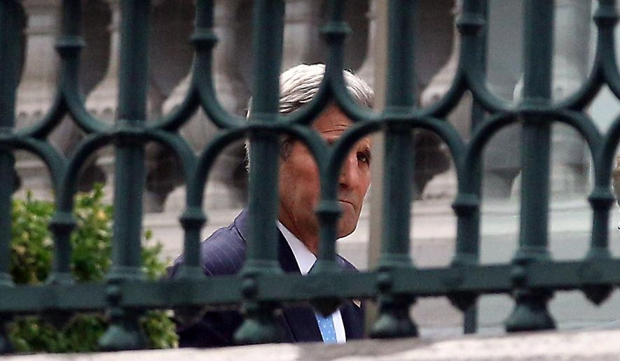 U.S. Secretary of State John Kerry walks in the garden of Coburg where closed-door nuclear talks with Iran take place in Vienna, Austria, Sunday July 12, 2015. (AP Photo/Ronald Zak)