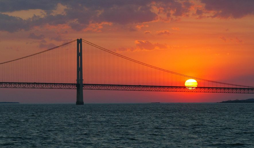 FILE - In this May 31, 2002 file photo, the sun sets over the Mackinac Bridge and the Mackinac Straits as seen from Lake Huron. The bridge is the dividing line between Lake Michigan to the west and Lake Huron to the east. Michigan's attorney general and chief environmental regulator issue a report Tuesday, July 14, 2015 on the safety of oil pipelines, including one stretching beneath an ecologically sensitive area linking Lakes Huron and Michigan. (AP Photo/Al Goldis, File)