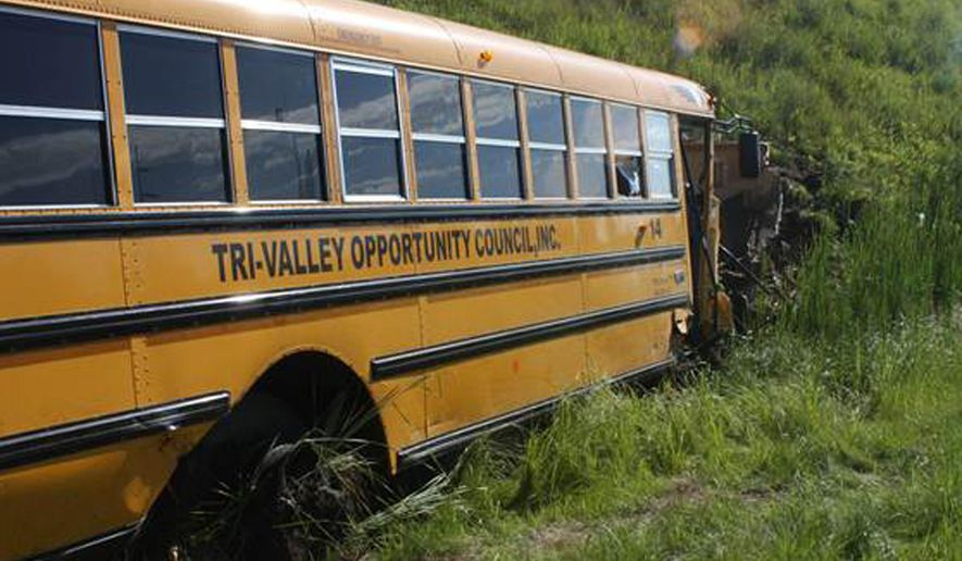This July 13, 2015 photo provided by Scott Tedrick shows a school bus crash near Granite Falls, Minn. Authorities say 11 children and 3 adults on the bus were injured, along the with driver and passenger of a car that collided with the bus. None of the injuries were life-threatening. (Scott Tedrick/Advocate Tribune via AP)