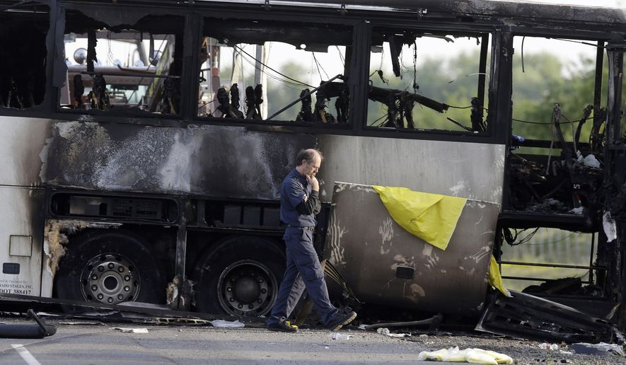 FILE - In this April 11, 2014 file photo, an official walks past the remains of a tour bus that was struck by a FedEx truck on Interstate 5 in Orland, Calif. Federal investigators are expected Tuesday, July 14, 2015, to announce the probable cause of the deadly crash between the truck and the bus carrying high school students. The Northern California crash and fire killed 10 and injured dozens. (AP Photo/Jeff Chiu, File)
