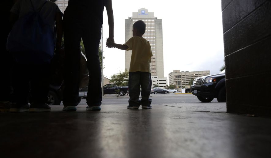 In this Tuesday, July 7, 2015, photo a young boy holds hands with his mother at a bus station after they were released from a family detention center in San Antonio. The group from El Salvador had been held at a family detention center after they were caught entering the country illegally. Women and children are being released from immigrant detention centers faster on bond, with many mothers assigned ankle monitoring bracelets in lieu of paying. (AP Photo/Eric Gay)
