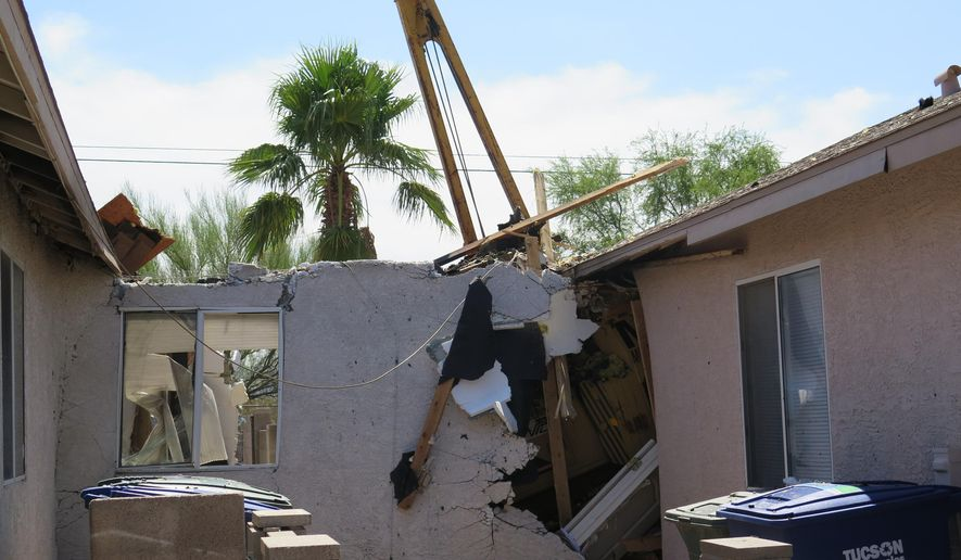 Extensive damage to two homes is seen after a stolen tractor crashed into them early morning Tuesday, July 14, 2015 in Tucson, Ariz. The tractor started a fire in the first home and then moved on to the second one before firefighters were able to turn it off. Both houses were total losses and six people were left homeless. (AP Photo/Astrid Galvan)