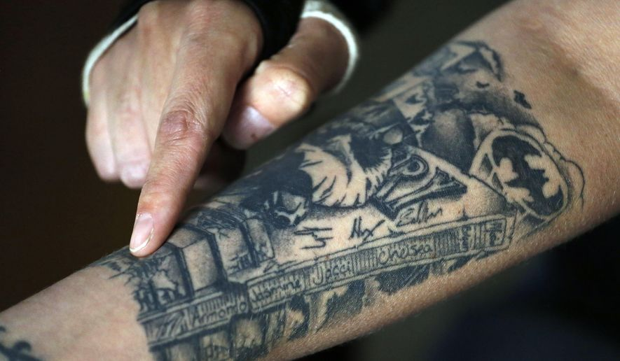 FILE - In this May 21, 2015 file photo, theater shooting attack survivor Christina Blache gestures to a tattoo memorializing the 12 people who were killed by James Holmes in the Aurora, Colo., theater killings, at her home in Northglenn, Colo. With closing arguments to take place on July 14, 2015, jurors in the Colorado theater shooting trial soon will retreat into the largest jury room in the courthouse to determine whether Holmes was legally insane at the time of the killing spree. (AP Photo/Brennan Linsley, file)