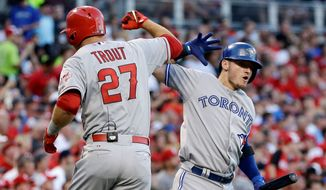 The American League's Mike Trout, of the Los Angeles Angels, high-fives Josh Donaldson, of the Toronto Blue Jays, after Trout hit a leadoff home run in the first inning of Tuesday's All-Star Game in Cincinnati. For coverage, see www.washingtontimes.com/sports. (Associated Press)