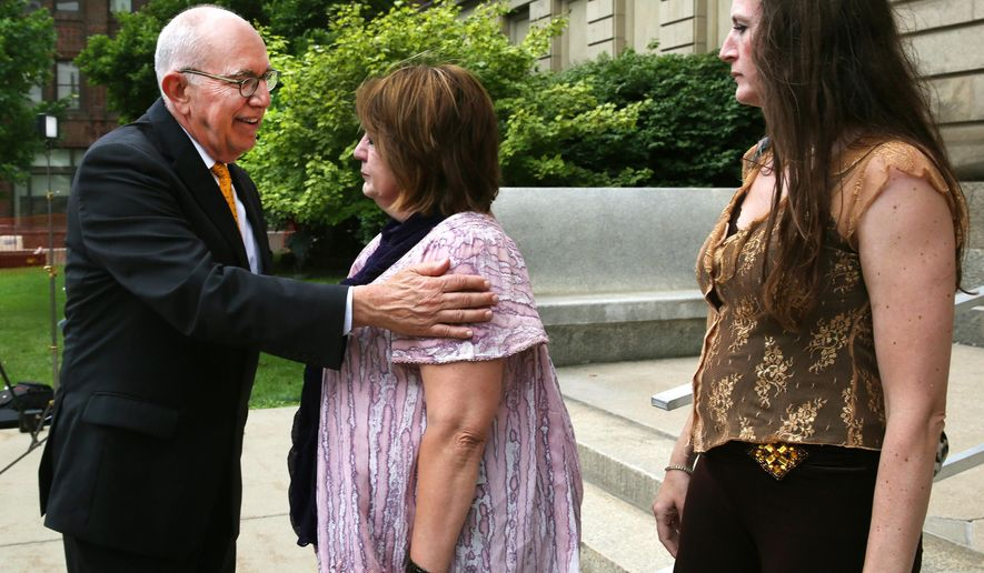 Elaine Sgorcea, mother of Richmond Hill victim Dion Longworth, is hugged by Marion County Prosecuting Attorney Terry Curry as she walks out of the St. Joseph County Courthouse after hearing the jury found Mark Leonard guilty of all 53 charges, including murder, on Tuesday, July 14, 2015, in South Bend, Ind.  A jury convicted Leonard of murder, arson and insurance fraud Tuesday for his role in a house explosion that devastated a subdivision nearly three years ago, killing a couple living next door.  At right is one of Dion Longworth's sisters. (Charlie Nye/The Indianapolis Star via AP)  NO SALES; MANDATORY CREDIT