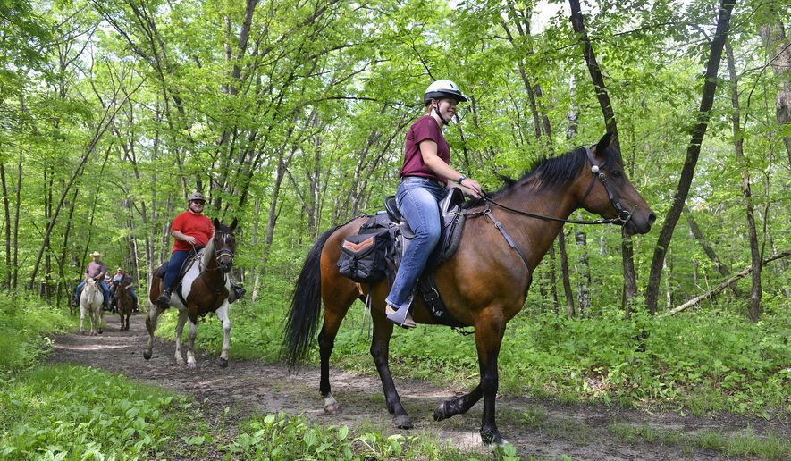 Sammy Schneider, 15, rides with her aunt, Christie Winkels  during a trail ride with the Riverside Trail blazers at Lake Maria State Park on June 7, 2015, in rural Monticello, Minn.  Riverside Trailblazers, which started in 2003, focuses on three things: trail rides, parades and event parking.  (Kimm Anderson/The St. Cloud Times via AP)  NO SALES