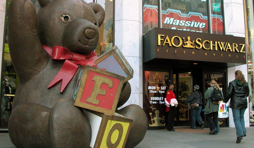 FILE - In this Nov. 10, 2003 file photo, customers pass a statue of a teddy bear and a doorman dressed as a toy soldier as they enter the FAO Schwarz on Fifth Avenue in New York.  The store is closing its doors for good on Wednesday, July 15, 2015, though it may reopen elsewhere in midtown Manhattan. Owner Toys R Us announced the decision in May, citing costs. (AP Photo/Rich Kareckas, File)