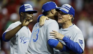 American League manager Ned Yost, of the Kansas City Royals hugs American League's Salvador Perez, of the Kansas City Royals after the MLB All-Star baseball game, Tuesday, July 14, 2015, in Cincinnati. The American League won 6-3. (AP Photo/John Minchillo)