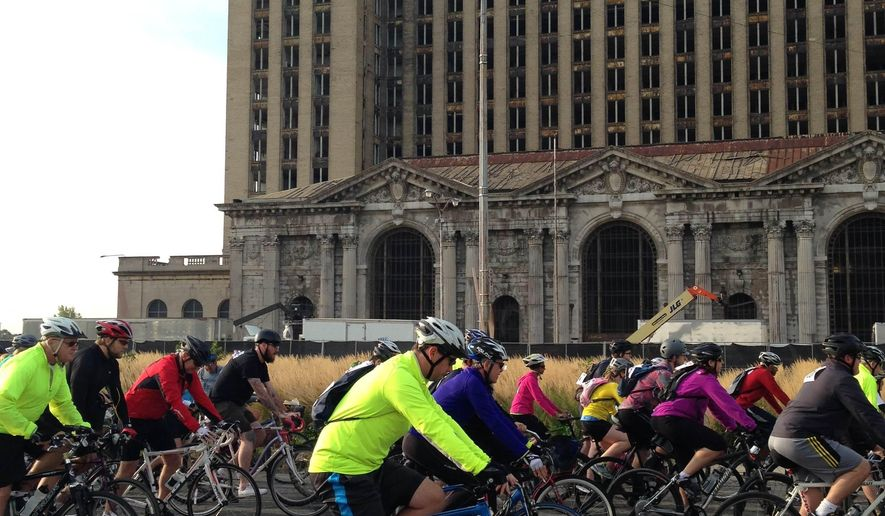 FILE - In this Sept. 20, 2014, file photo, bicyclists pass the Michigan Central Depot during the Tour de Troit ride in Detroit. The event billed by organizers as Michigan's biggest cycling ride is expected to draw even more participants. More than 2,100 people have signed up to ride Sept. 19, 2015, in the 14th annual Tour de Troit. The event has raised nearly $200,000 for greenways and other non-motorized projects in Detroit, helping develop more than 17 miles of bike lanes. (AP Photo/Roger Schneider, File)