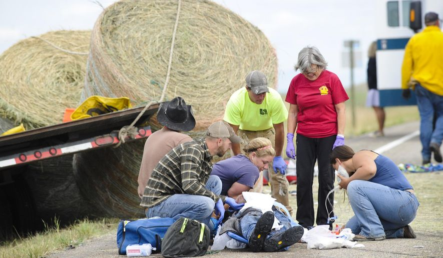 Emergency personnel work at the scene of a fatal head-on collision between two trucks on Highway 287, north of Wolf Creek, Mont. on Wednesday, July 15, 2015. (Thom Bridge/The Independent Record via AP)