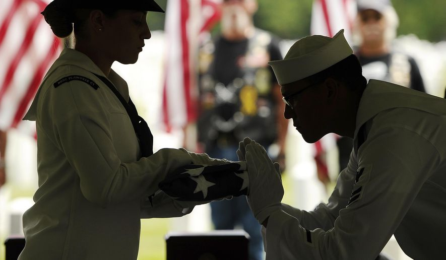 U.S Navy Fireman, Machinists Mate Striker Aixa Cruz, left, and U.S Navy Hospital Corpsman 2nd Class James Stringer, right, fold the flag for unclaimed Navy veteran David Clinton at State Veteran's Cemetery, Wednesday, July 15, 2015, in Middletown , Conn. Four Connecticut veterans received long overdue burials with military honors, years after they died and their remains went unclaimed. The men served in the military decades ago and all died within the past 13 years. (AP Photo/Jessica Hill)