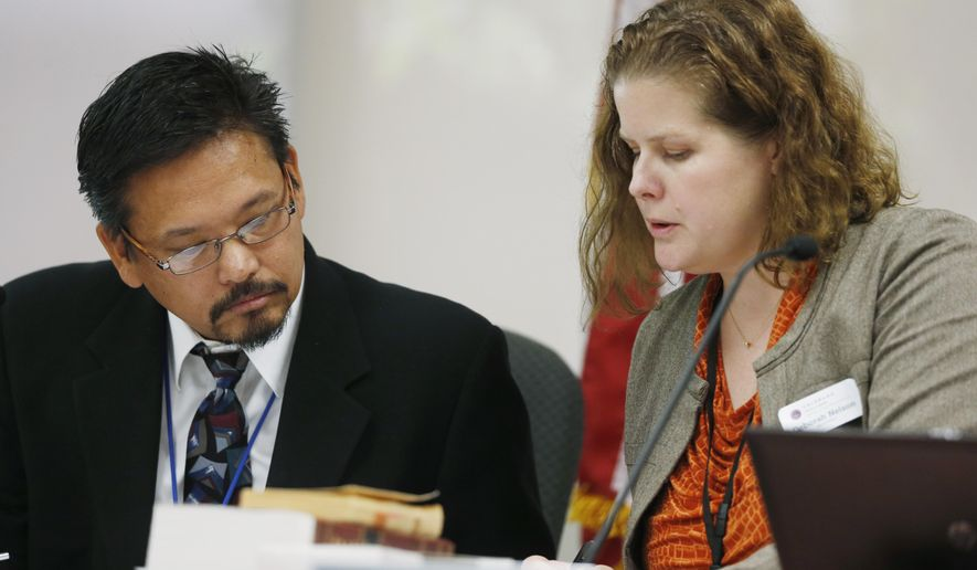 Dr. Ray Estacio, left, a member of the Colorado Board of Health, confers with Deborah Nelson, board administrator, during testimony to add post-traumatic disorder to the list of ailments eligible for treatment with medical marijuana during a hearing before the board Wednesday, July 15, 2015, in Denver. If approved, Colorado would become the 10th state to consider PTSD a qualifying condition for medical pot.  (AP Photo/David Zalubowski)