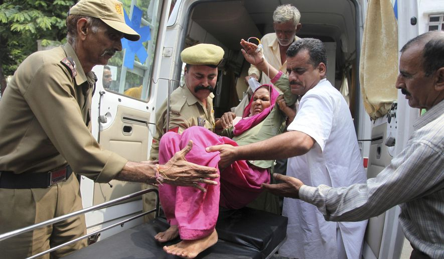 An Indian civilian woman injured in exchange of fire by troops on the India Pakistan border is brought for treatment at the government medical college hospital in Jammu, India, Wednesday, July 15, 2015. Indian and Pakistani troops exchanged fire in the disputed Himalayan region of Kashmir on Wednesday, killing a woman and wounding at least four other people on the Indian side, officials said. (AP Photo/Channi Anand)