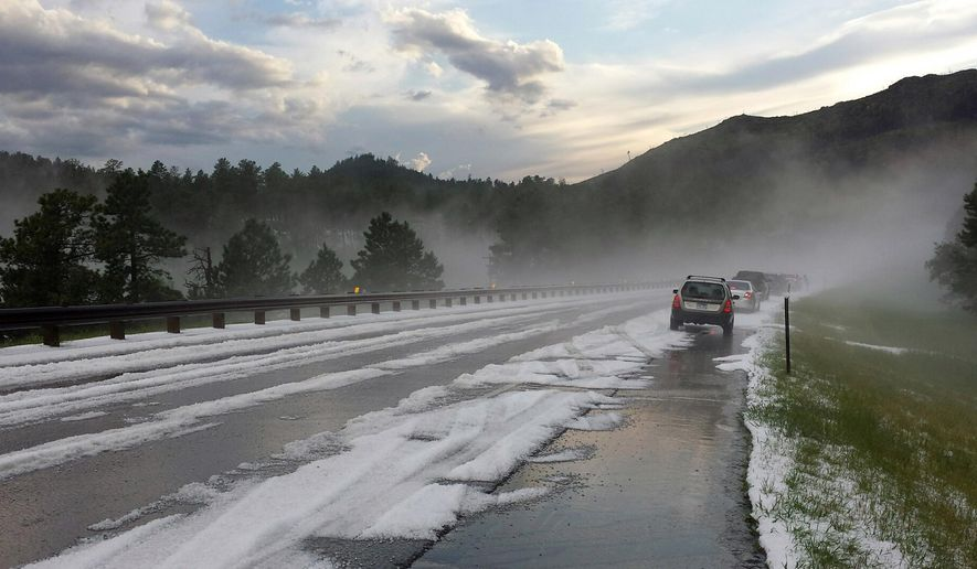 This Tuesday, July 14, 2015 photo provided by Karen Maudlin shows cars on the side of the road after a hailstorm near Rockerville, South Dakota. A brief but intense hailstorm Tuesday dropped as much as 4 inches of slippery pellets in a South Dakota city prompted officials to call out snowplows in the middle of summer. (Karen Maudlin via AP)