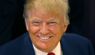 In this June 29, 2015, file photo, Republican presidential candidate Donald Trump smiles for a photographer before he addresses members of the City Club of Chicago, in Chicago. (AP Photo/Charles Rex Arbogast, File)