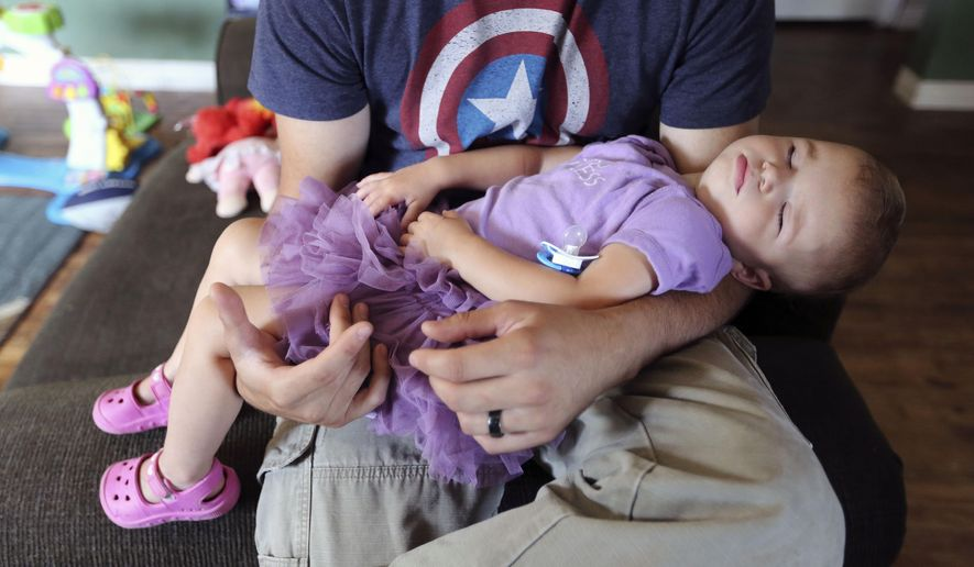 ADVANCE FOR WEEKEND EDITIONS JULY 18-19 - In this Tuesday, July 7, 2015 photo, Oliver Prescott holds his 1-year-old daughter, Olivia, who had surgery for craniosynostosis (a birth defect that affects the baby's skull), at their home in Scio, Ore. Craniosynostosis, occurs when an infant's skull sutures close prematurely. (Danielle Peterson/Statesman-Journal via AP) MANDATORY CREDIT