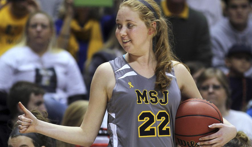 FILE - In this Nov. 2, 2014, file photo, Mount St. Joseph's Lauren Hill gives a thumbs-up as she holds the game ball during her first NCAA college basketball game, against Hiram University, at Xavier University in Cincinnati. Hill will be honored at the ESPY Awards. Hill inspired people with her fight against brain cancer and raised over $1.5 million for cancer research before she died April 10. Her life will be celebrated in a special presentation at the ESPYs on Wednesday night, July 15, 2015. The former Division III women's basketball player just wanted to play one game in college. (AP Photo/Tom Uhlman, File)