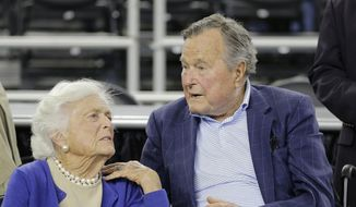 In this March 29, 2015, file photo, former President George H.W. Bush and his wife Barbara Bush, left, speak before a college basketball regional final game between Gonzaga and Duke, in the NCAA basketball tournament in Houston. (AP Photo/David J. Phillip, File)