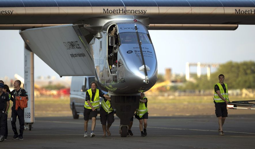 In this July 3, 2015, file photo, ground crew push the Solar Impulse 2, a solar-powered airplane, toward the hangar after landing at the Kalaeloa Airport in Kapolei, Hawaii. The Solar Impulse team said in a news release early Wednesday, July 15, 2015, that they are suspending the around-the-world journey in Hawaii, after the plane suffered battery damage during its flight to the islands. (AP Photo/Marco Garcia, File)