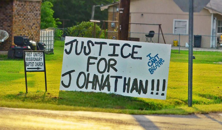 In this July 11, 2015 photograph, sign of support for Jonathan Sanders, a black man who is believed to have died after a physical encounter with a white police officer, hangs on a corner in Stonewall, Miss. A couple hundred people participated in a prayer vigil and march in Stonewall, on Saturday. The participants walked from a neighborhood ball park to the area where it is believed Sanders died on July 8. (Jennifer Bozeman/The Clarke County Tribune, via AP) MANDATORY CREDIT
