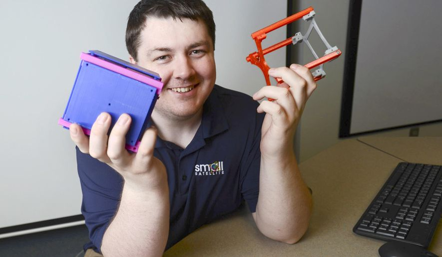In this June 8, 2015 photo provided by the University of North Dakota, Jeremy Straub, a computer science Ph.D. candidate who is coordinating the CubeSat project at the university, holds one completed CubeSat and one starting to be built in Grand Forks. The 2-pound miniature satellite that students have been working on for nearly five years has been approved for launch by NASA, which ranked the project as the best of its kind in the nation for the last year. The so-called CubeSat will be North Dakota's first spacecraft to orbit the earth. It will catch a ride on a supply trip heading to the International Space Station sometime next spring. (Jackie Lorentz/University of North Dakota via AP)