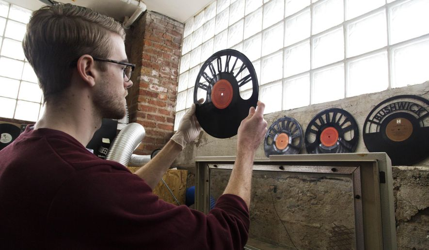 In this photo taken, March 12, 2015, Will Haude examines a record that he has passed through a laser cutter at Wrecords By Monkey in the Brooklyn borough of New York.  The company cuts and shapes the lacquered discs into jewelry, clocks, wall art and other novelties. (AP Photo/Mark Lennihan)