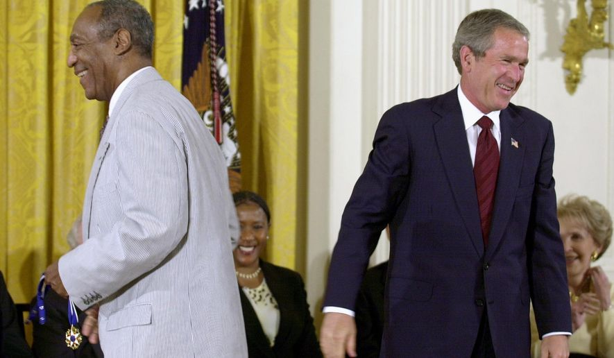FILE - In this July 9, 2002 file photo, President George W. Bush lets out a laugh after failing to get the clasp together on Bill Cosby's Presidential Medal of Freedom, which he holds, after Bush tried to put on the entertainer, in the East Room of the White House in Washington. President Barack Obama is rejecting the idea of revoking Cosby's Presidential Medal of Freedom because of sexual misconduct allegations. Obama says there's no precedent or mechanism to take back the medal. He declined to talk about the specific allegations against Cosby because there are pending legal matters. (AP Photo/Kenneth Lambert, File)