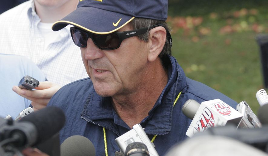 "FILE - In this Aug. 9, 2005, file photo, then-Michigan head football coach Lloyd Carr answers reporters  questions during practice in Ann Arbor, Mich. The University of Michigan's new apparel and equipment deal with Nike is worth $169 million, with a nearly even split between annual cash and apparel value. The deal, which begins in August 2016, was announced last week, and Michigan released financial details Wednesday, July 15, 2015. ""Nike is especially proud to partner with the Wolverines and have the opportunity once again to work with Michigan student-athletes, coaches, and staff,"" said Joaquin Hidalgo, vice president and general manager of Nike North America.  (AP Photo/Tony Ding, File)"