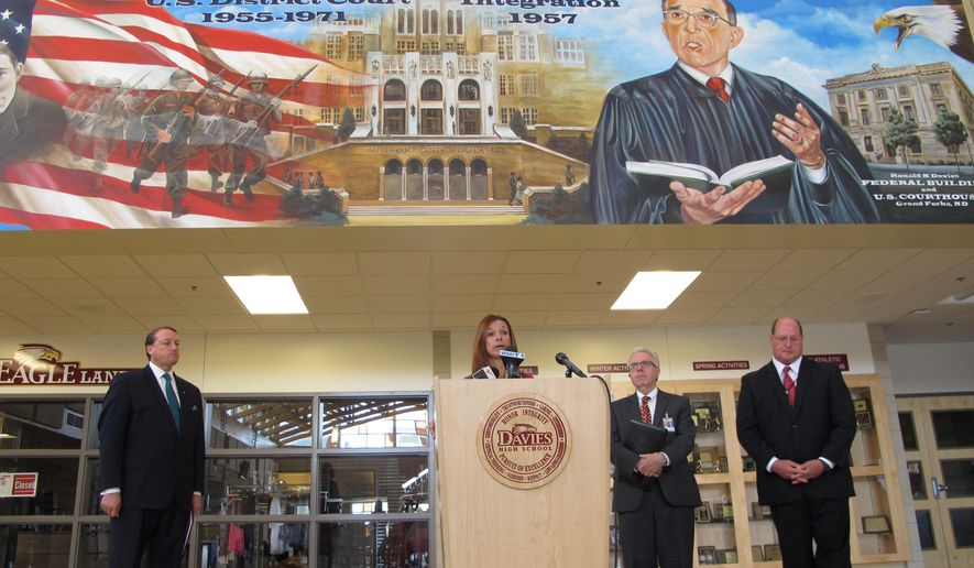 North Dakota Superintendent of Public Instruction Kirsten Baesler speaks about teacher training below a mural on the wall of Davies High School in Fargo, N.D., on Wednesday, July 15, 2015. Joining Baesler were from left, Marcus Lingenfelter, a vice president for the National Math and Science Initiative; David Flowers, West Fargo superintendent of schools; and Jeff Schatz, superintendent of Fargo public schools. (AP Photo/Dave Kolpack)